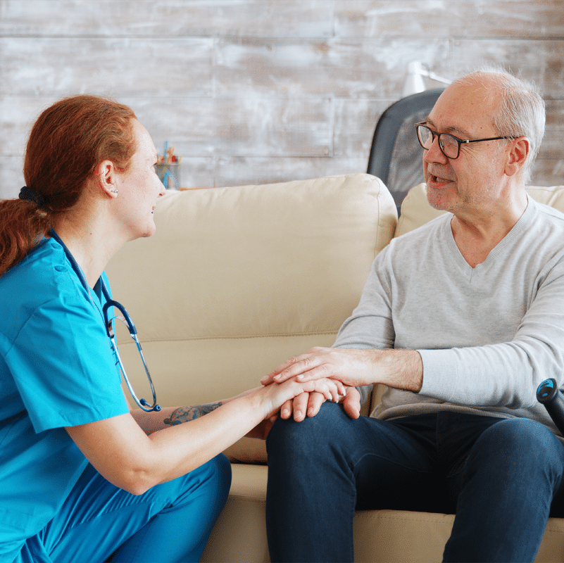 Pfleger*in hält die Hand eines Patienten